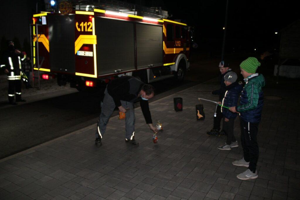 Ortsteilbürgermeister Lippmann verteilt die kleinen Naschbeutel an die Kinder.